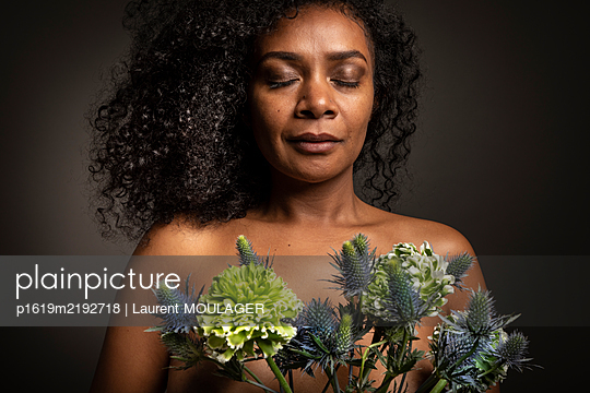 Curly hair serene woman with here eyes closed holding fresh flowers - p1619m2192718 by Laurent MOULAGER
