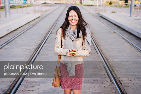 Happy woman with smart phone standing amidst railway tracks - p300m2274092 by Eva Blanco