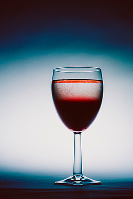 Glass full of red wine against white background - p1057m1564503 by Stephen Shepherd