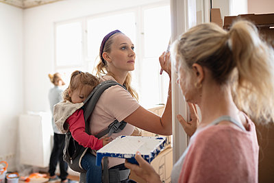 DIY mother painting with sleeping baby daughter in baby carrier - p1192m2016763 by Hero Images