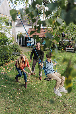 Son swinging in garden with parents pushing him - p300m2167304 by Kniel Synnatzschke