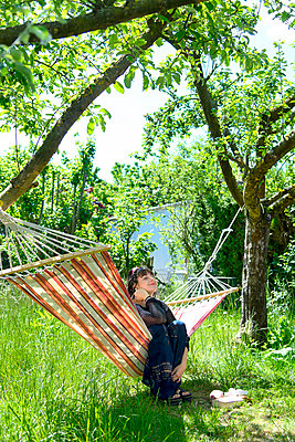 Young woman relaxing in a hammock - p427m2203613 by Ralf Mohr