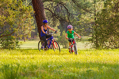 Mother and daughter riding mountain bikes in meadow - p555m1464277 by Michael DeYoung