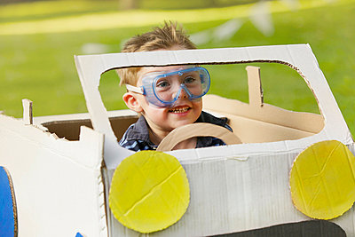 Boy Wearing Goggles Driving Cardboard Car - p669m713973 by Jutta Klee photography