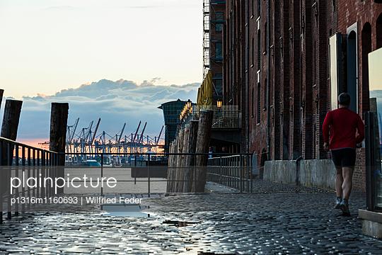 Jogger läuft an einem Speicher entlang, Große Elbstraße, Hamburg, Deutschland - p1316m1160693 von Wilfried Feder