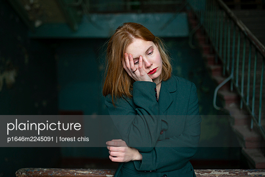 Sad teenage girl with red hair in the staircase - p1646m2245091 by Slava Chistyakov