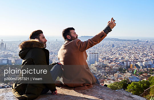 Man taking selfie with boyfriend while sitting on observation point, Bunkers del Carmel, Barcelona, Spain - p300m2257321 by Veam