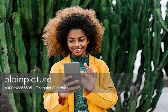 Smiling Afro woman using smart phone while standing against cactus plants - p300m2265805 by Ezequiel Giménez
