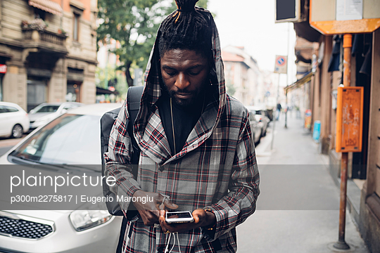 Young man using smart phone on footpath - p300m2275817 by Eugenio Marongiu