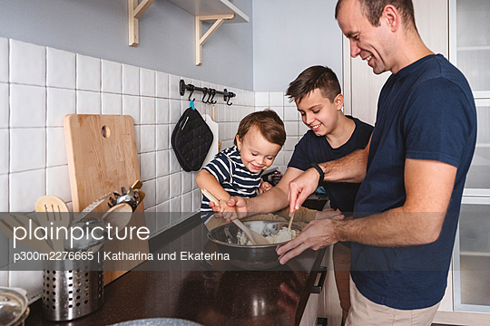 Cheerful sons helping father to prepare food in kitchen at home - p300m2276665 by Katharina und Ekaterina