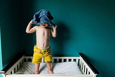 Boy removing shirt while standing in bunkbed against wall - p1166m1186123 by Cavan Images