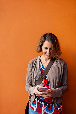 Smiling woman using smart phone while standing against orange wall - p1166m2067933 by Cavan Images