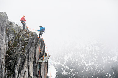 Climbers rappelling onto portaledge on a vertical cliff face. - p1166m2212656 by Cavan Images