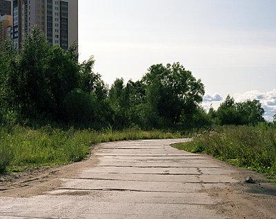 Verlassene Straße in der Nähe eines Wohnturms - p1409m1465896 von margaret dearing