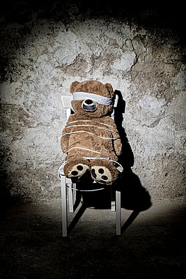 Teddy bear as kidnap victim on a chair in a cellar - p1625m2228449 by Dr. med.
