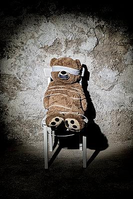 Teddybär als Entführungsopfer auf einem Stuhl im Keller - p1625m2228449 von Dr. med.