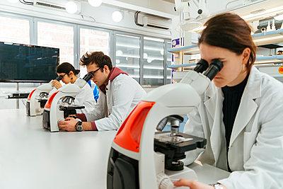 Laboratory technicians using microscopes in lab - p300m1416484 by Zeljko Dangubic