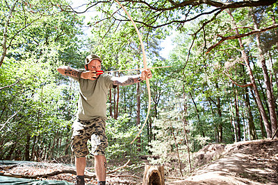 Man shooting with bow and arrow in the forest - p300m1499460 by Michelle Fraikin