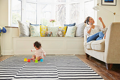 Woman with baby daughter reclining on sofa making smartphone call - p429m1448137 by Emma Kim