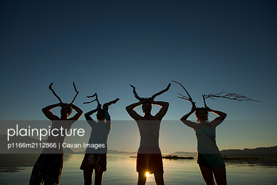 Four friends pretending to make antlers with found sticks at a lake - p1166m2112866 by Cavan Images