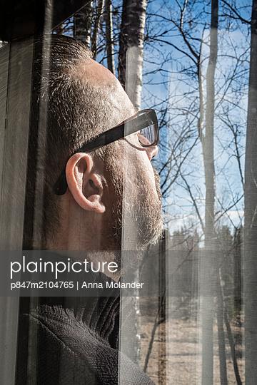 Man's Face Seen Through Glass Window, Sweden    - p847m2104765 by Anna Molander