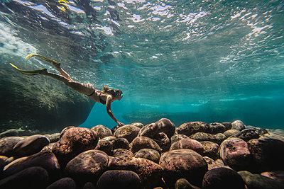 Side view of woman diving undersea - p1166m2067149 by Cavan Images