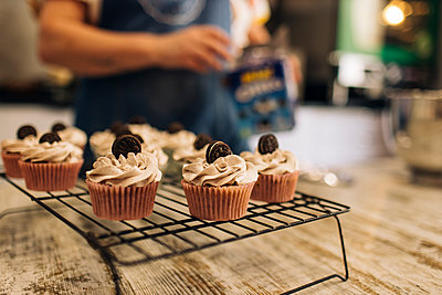 Close-up of cupcakes on rack with female baker in background at shop - p300m2202655 by Gala Martínez López