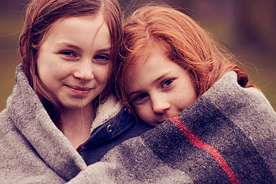 Portrait of girls wrapped in a blanket outdoors - p429m802956f by Emma Kim