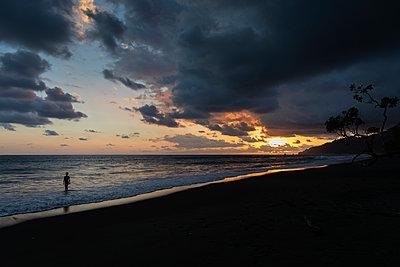 Urlauber bewundert den Sonnenuntergang an der Playa Madrigal - p590m1564526 von Philippe Dureuil