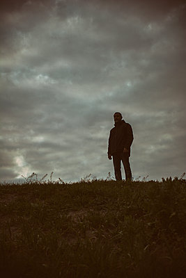Man standing outdoors looking away  - p794m1590957 by Mohamad Itani