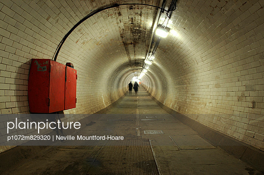 Two figures in the distance of foot tunnel - p1072m829320 by Neville Mountford-Hoare