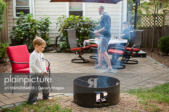 a little boy roasts marshmallows in backyard with family - p1166m2084823 by Cavan Images