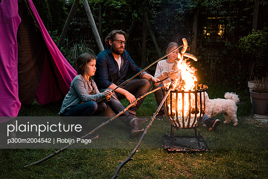 Man and two girls grilling sausage over camp fire in garden - p300m2004542 von Robijn Page