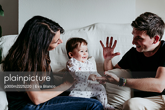 Mother and son sitting while father doing high five sitting on sofa at home - p300m2225220 by Eva Blanco