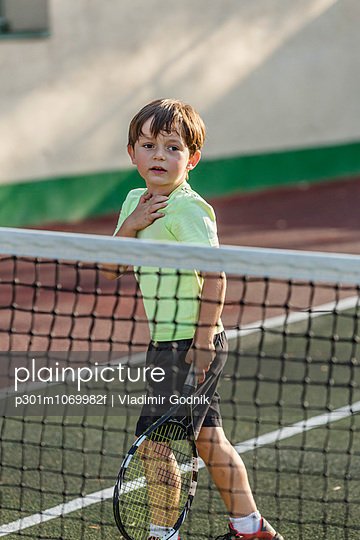 Boy holding tennis racket while standing on field