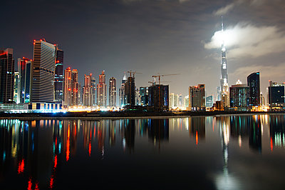 Low angle view of Burj Khalifa amidst illuminated city against sky - p1166m1544355 by Cavan Social