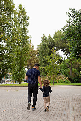 Rear view of father and son walking hand in hand - p300m2081210 von Mauro Grigollo