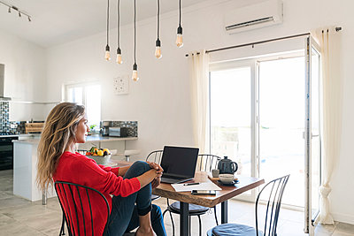 Woman using laptop on dining table in modern home - p300m2104307 by Steve Brookland
