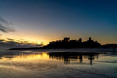 Bamburgh Castle silhouetted at dusk; Bamburgh, Northumberland, England - p442m2101141 by John Short