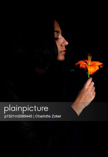 Young woman holding flower - p1521m2089445 by Charlotte Zobel