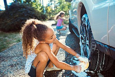 Girls washing car in driveway - p1166m1225979 by Cavan Images