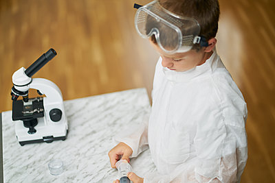 young boy looks at camera dressed in white coat prepares to observe by - p1166m2153875 by Cavan Images