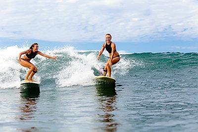 Two girls surfing in ocean - p300m1450022 by Konstantin Trubavin