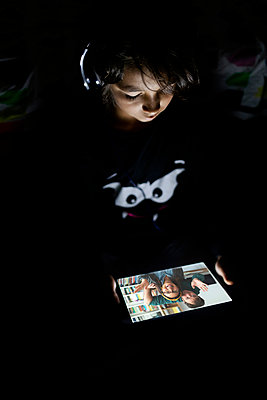 Boy sitting in his dark room at home using headphones and digital tablet for video chat - p300m2189536 by Valentina Barreto