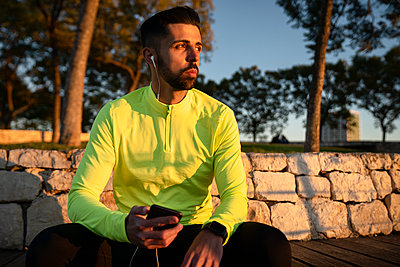 Male athlete listening music at park during sunset - p300m2250295 by Albert Martínez