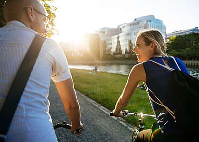 Germany, Berlin, Man and woman cycling in city - p352m1187287 by Lars Hollander