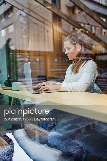 Woman using laptop in cafe - p312m2191255 by Dayfotografi