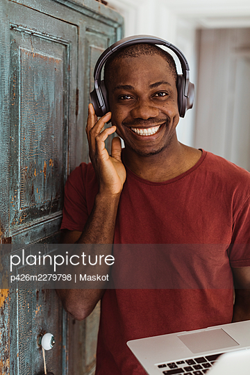 Portrait of smiling male professional with headphones at home - p426m2279798 by Maskot