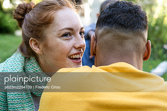Smiling young couple having fun while sitting in park - p623m2294739 by Frederic Cirou