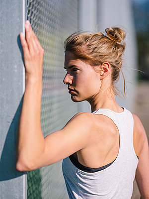Germany, Hannover, Athletic woman doing stretching exercise on fence - p1600m2230796 by Ole Spata